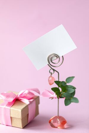 Gift box with a pink bow. Gift for Valentines Day or March 8th. Business card, holiday card on a pink background.