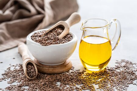 Flaxseed oil in a bottle and ceramic bowl with brown flax seeds and wooden spoon on a white background.