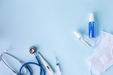 medical concept on a blue background. stethoscope, pills, tablet, notepad, sheet of paper, pen. Medical mask