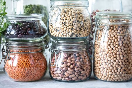 Set of different legumes in glass jars on a wooden table. A source of protein for vegetarians. Healthy eating concept Standard-Bild