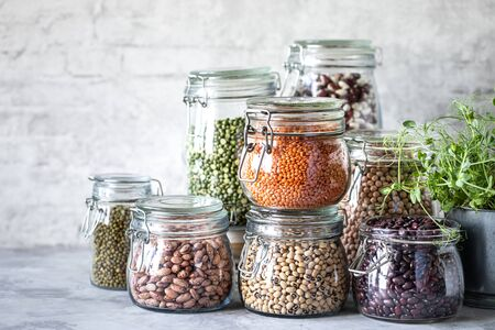 Set of different legumes in glass jars on a wooden table. A source of protein for vegetarians. Healthy eating concept. copy space