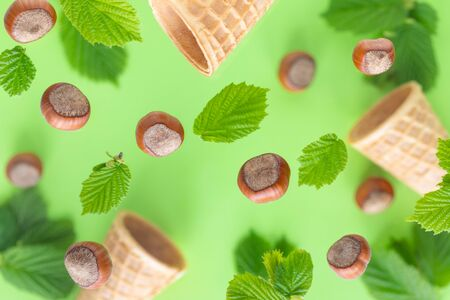 Falling hazelnuts with green leaves and wafer cups for ice cream on a colored background, selective focus. Top view, flat lay.