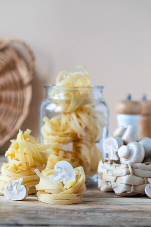 Different types of italian pasta in glass jars on a yellow wooden table.