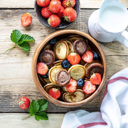 Tiny pancake cereal and chocolate mini pancakes in a wooden bowl with honey and strawberries on a wooden background. Top view. Copy space Фото со стока