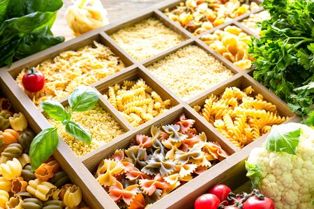 Different types of italian uncooked pasta in wooden box, whole wheat pasta, pasta, spaghetti, noodles, tagliatelle. Top view.