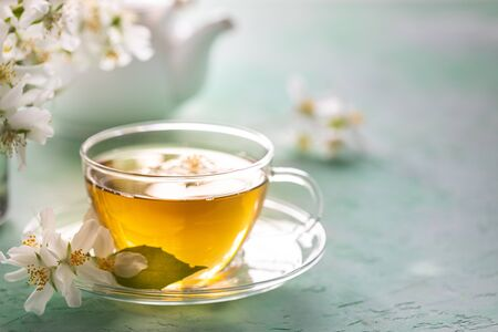 Jasmine flower tea on green stone, spa concept. Copy space Banque d'images