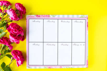 Glider with notes and to-do list on a yellow background with pink stationery and flowers. Business concept.