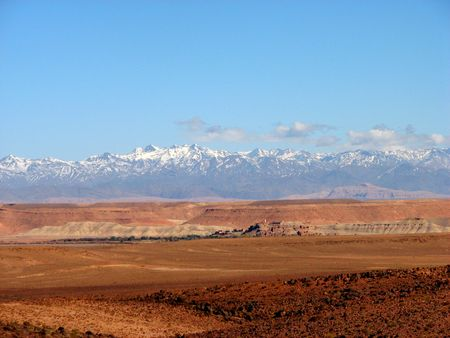 Marocco: rocky landscape in south Marocco with snowed mountains in the background