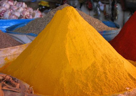 displayed: close-up of yellow spices displayed in a market