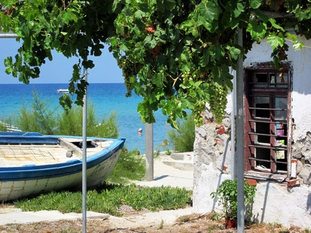 View of Aegean Sea with old blue and white fisherman boat on sand underneath a grape bush in front of ruinous house in Greece, Chalkidiki