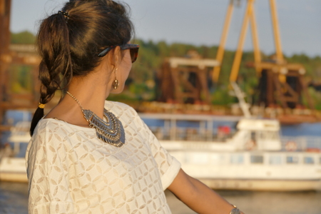 portrait of a beautiful girl on a background of the iron framework of the bridge.