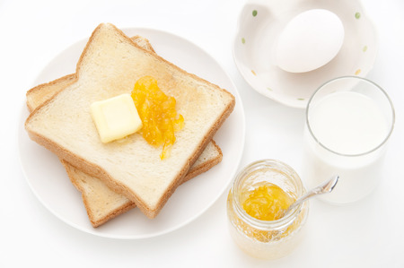 Breakfast bread butter and marmalade and milk