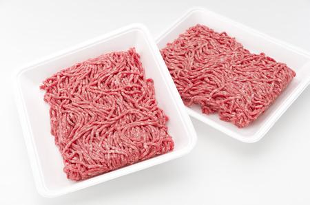 白い背景に分離された白いスチロール トレイにみじん切りにした生の牛肉の肉。