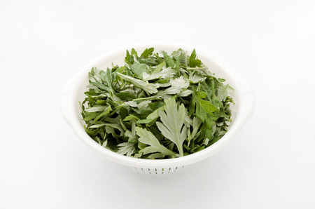 eliminate: Fresh green mugwort leaves in a white basket on a white background. Stock Photo