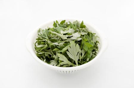 ajenjo: Fresh green mugwort leaves in a white basket on a white background. Foto de archivo