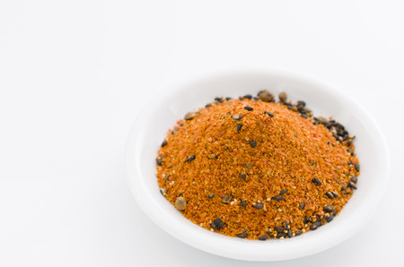 Shichimi pepper. Blend of seven spices in Small dish isolated on white background Stock Photo