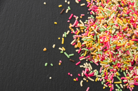 Colored sprinkles, decoration for cake and bekery, Colored sprinkles on black plate 写真素材