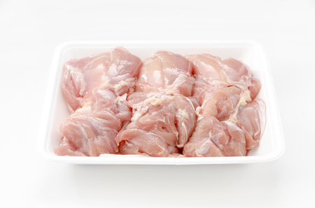 Raw chicken thighs in a packaging tray.