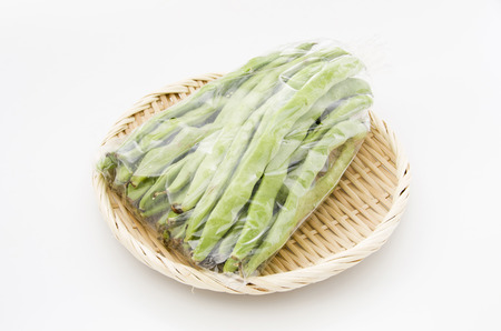 Flat green beans in plastic bag on bamboo sieve