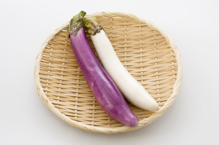 Long thin white eggplant and Long thin Purple eggplant on bamboo sieve isolated white background