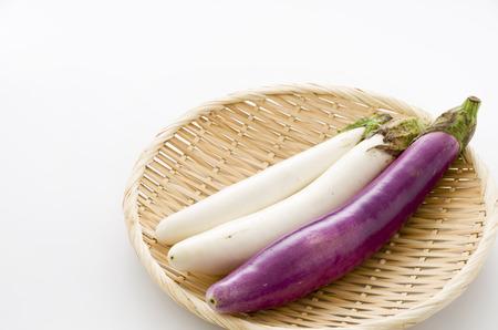 Long thin white eggplant and Long thin Purple eggplant on bamboo sieve isolated white background