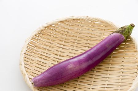 Long thin Light purple eggplant on bamboo sieve isolated white background Stock Photo