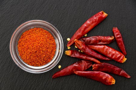 Cayenne pepper powder in a Stacking bowl with Capsicum annuum isolated on stone plate.