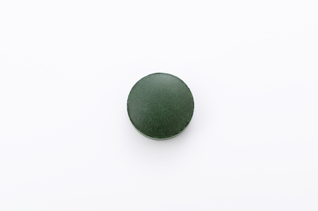 Green pills, Spirulina tablets on white background