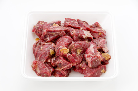 Seasoned raw chopped beef meat pieces on stainless steel tray on white background. Chuck eye roll. 스톡 콘텐츠