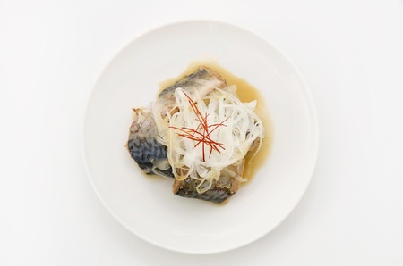 Boiled mackerel with onions and red pepper on white dish on white background. Imagens
