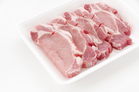 Raw pork meat in foam tray on white background
