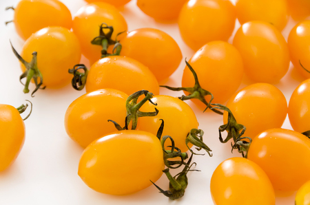 Fresh yellow cherry tomatoes on white background