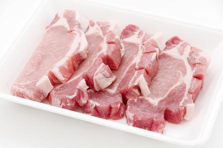 Raw pork meat in foam tray on white background