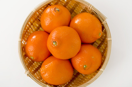 Minneola (Hybrid of Mandarin and Grapefruit) on a bamboo colander on white background, also Called Honeybell.