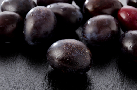 Fresh purple plums on black Stone plate