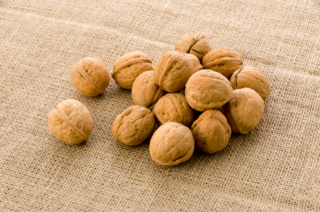Walnuts on Burlap background. Imagens
