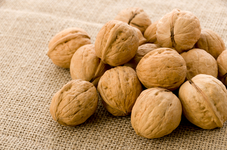 Walnuts in the wooden bowl, background on burlap. Stock Photo