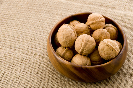 Walnuts in the wooden bowl, background on burlap. Imagens