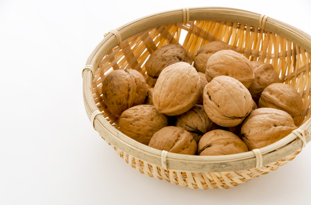 Walnut in a bamboo Sieve on a white background