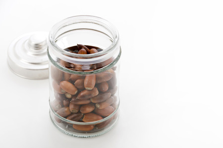 Glass jar with acorns on white background
