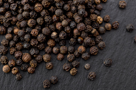 black pepper on black stone plate Фото со стока