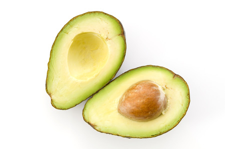 Ripe organic avocados half with seed on white background.