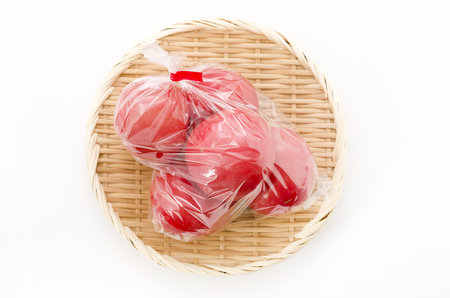 Ripe red Tomatoes in Plastic bag on bamboo colander.