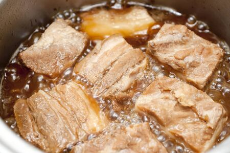 Boil the pork in a pot. Japanese food, Okinawa cuisine Rafuthy. Okinawan-style stewed pork cubes, pork belly, stewed in awamori, soy, dashi broth, and sugar.