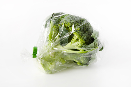 fresh broccoli in transparent plastic bag on white background Stock Photo