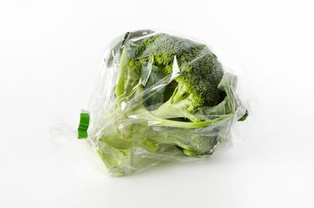 fresh broccoli in transparent plastic bag on white background 免版税图像