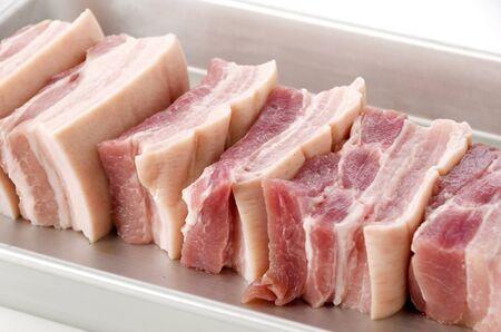fresh Pork belly on a Aluminum tray on white background. Stock Photo