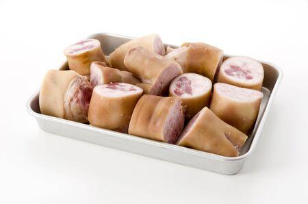 fresh raw pig's feet on aluminum tray on white background