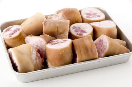 fresh raw pig's feet on aluminum tray on white background Stock Photo