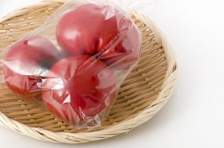 Ripe red Tomatoes in Plastic bag on bamboo colander Archivio Fotografico